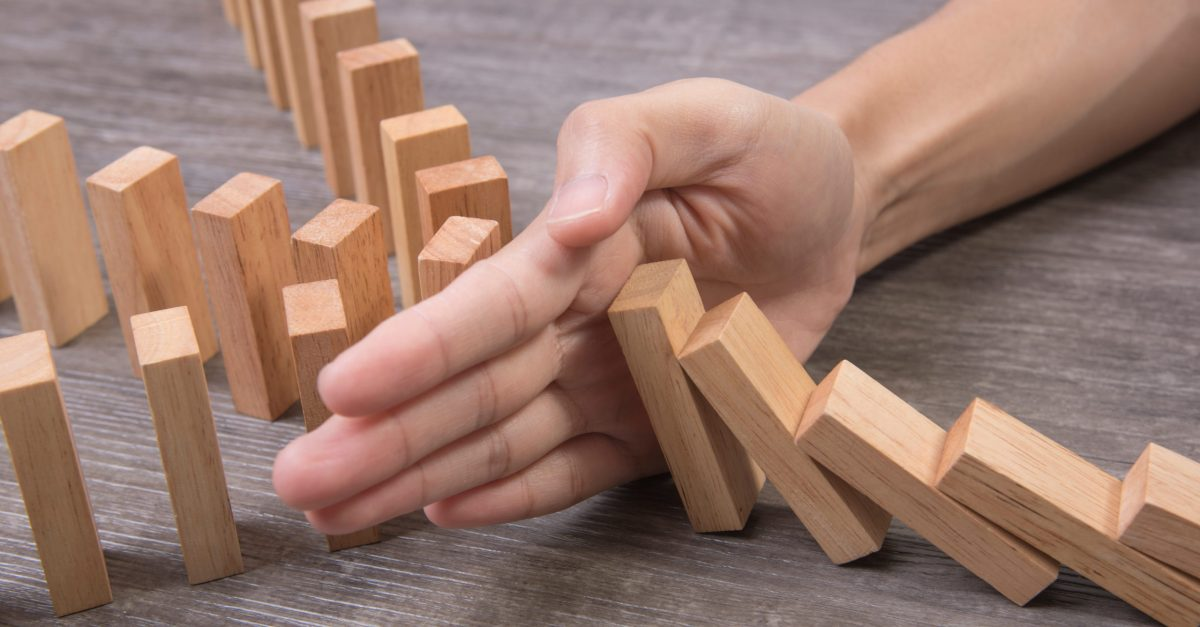 Hand,Stopping,Wooden,Block,Domino.,Concept,Prevent,And,Solution.